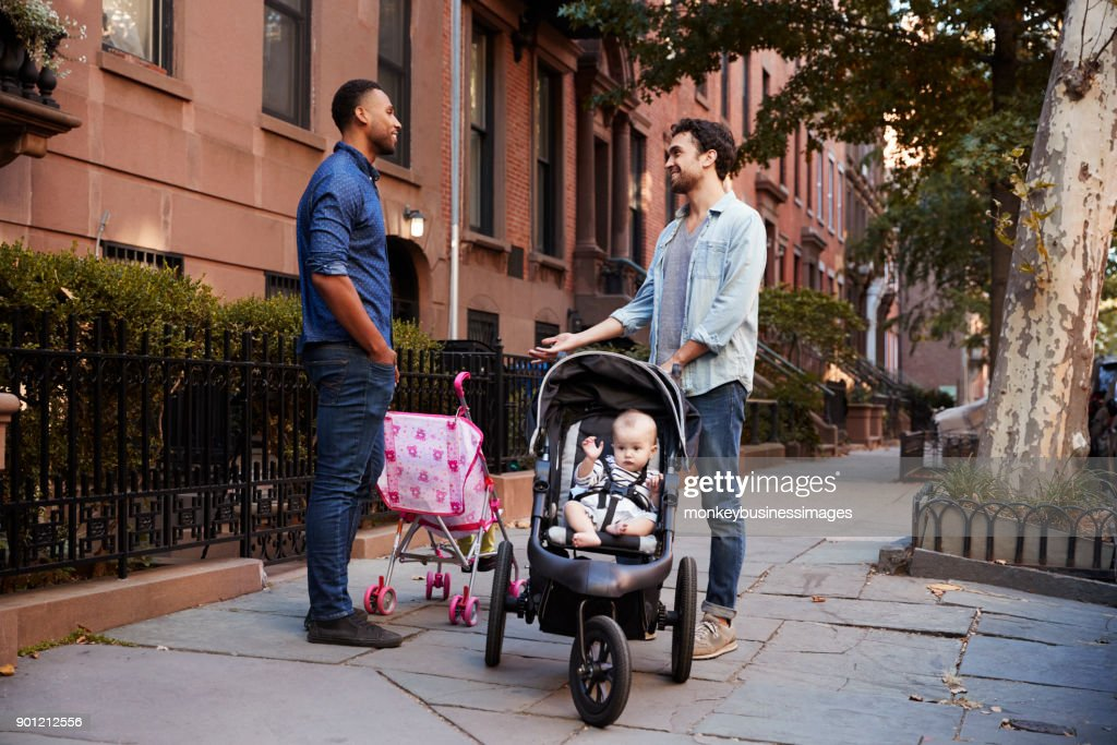 Two father friends with two kids talking in the street : Stock Photo