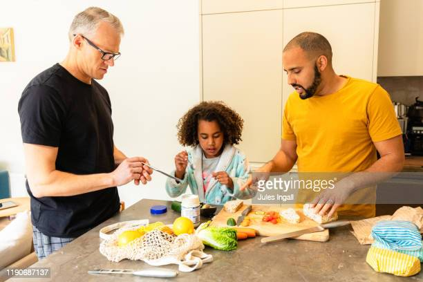 two fathers in the kitchen with their daughter - thisisaustralia stock pictures, royalty-free photos & images