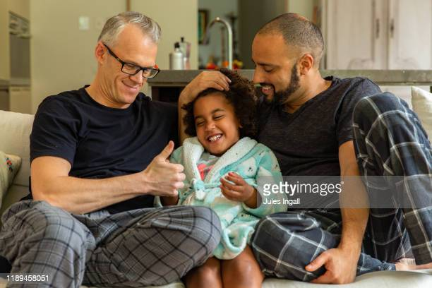 two fathers laughing on a couch with their daughter - lgbtq  and female domestic life fotografías e imágenes de stock