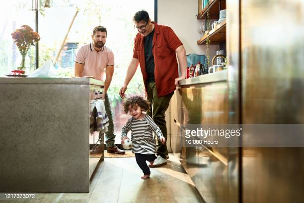 two fathers watching toddler playing with ball in kitchen - kitchen stock pictures, royalty-free photos & images