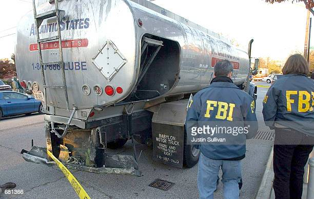 Two FBI agents inspect the rear end of a truck that was hit by part of the engine that fell off American Airlines Flight 587 that crashed November...