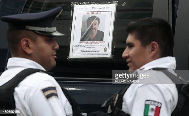 Two Federal Police officers stand next to a patrol car with a picture of fugitive drug lord Joaquin El Chapo Guzman's on its window in Acapulco...