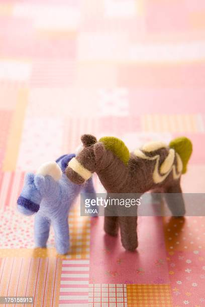 Two Felt Toy Horses on Pink Paper