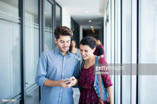 Two female and male colleagues looking at mobile phone