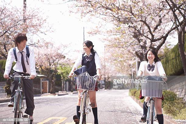 Two female and one male high school students (17-18) on bicycles on street