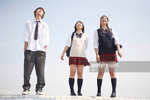 two female and one male high school students (17-18) on top of wall, looking up at sky - japanese short skirts stock photos and pictures