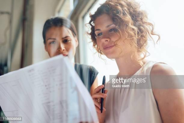 two female architects holding blueprints in new office. - weibliche angestellte stock-fotos und bilder