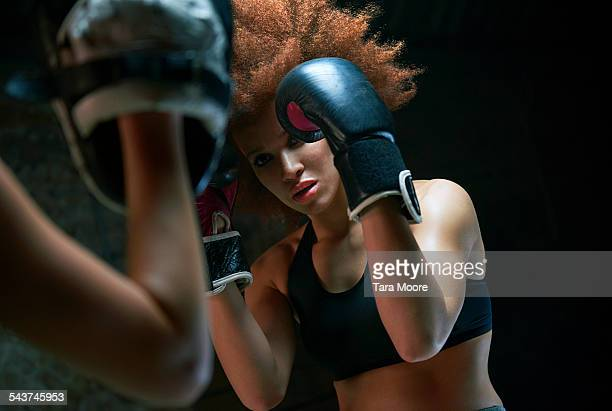 two female athletes boxing brick background - dominant woman stock pictures, royalty-free photos & images