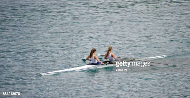 Two female athletes rowing across lake in late afternoon