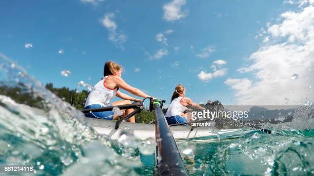 two female athletes rowing across lake in late afternoon - extra long stock pictures, royalty-free photos & images