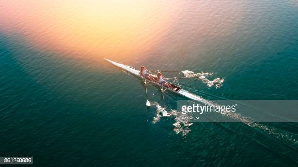 two female athletes sculling on lake in sunshine - rowing stock pictures, royalty-free photos & images