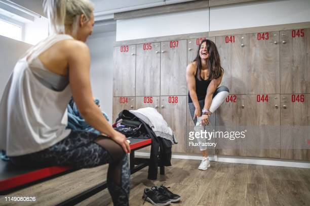 two female athletes talking to each other after a hard session of exercising - locker room stock pictures, royalty-free photos & images