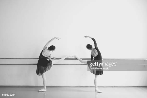Zwei weibliche Ballett-Tänzer posiert neben einem Barre.