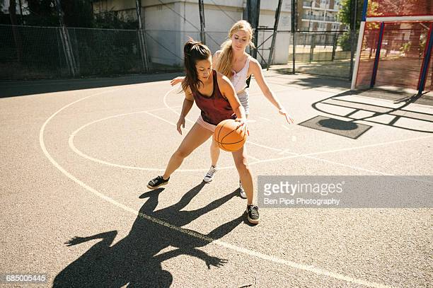 Two female basketball players practising on basketball court