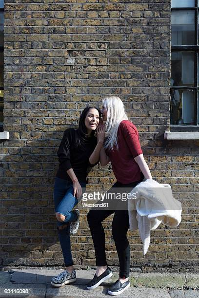 Two female best friends whispering at brick building