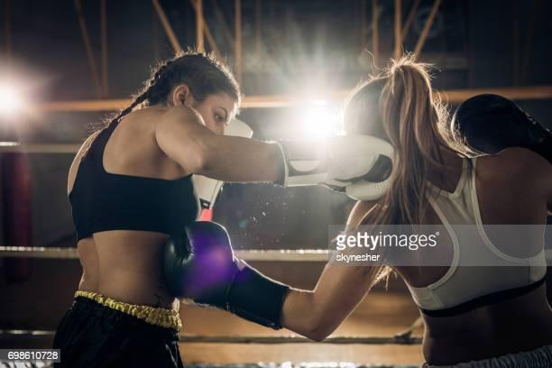 dois pugilistas femininas lutando durante uma luta de boxe em um ringue. - boxe feminino - fotografias e filmes do acervo
