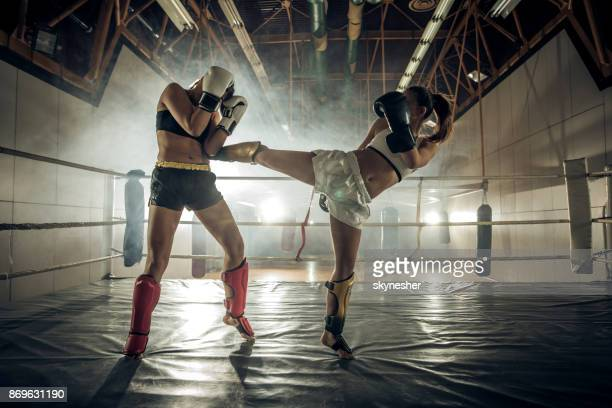 Two female boxers having a match in a boxing ring.
