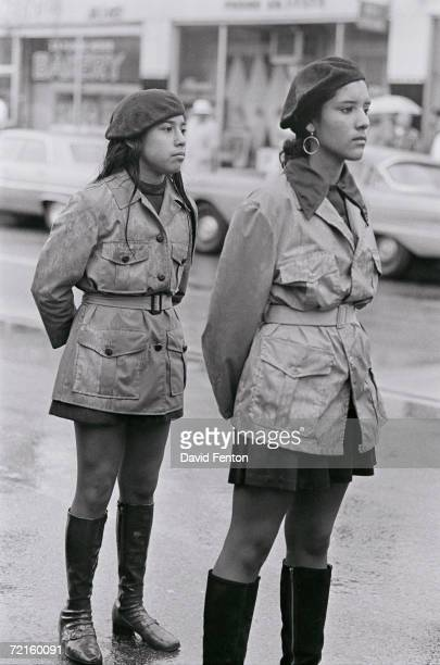 Two female Brown Berets a Chicano activist group stand together in matching uniforms during a National Chicano Moratorium Committee march in...