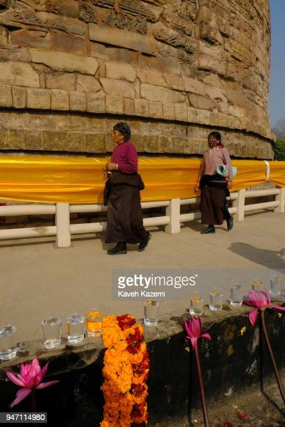 Two female Budhist pilgrims circle around the Dhamek Stupa going past the flowers incense candles and plastic cups of water laid on the rim of the...