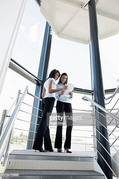 two female business colleagues standing in office staircase - hugh sitton photos et images de collection