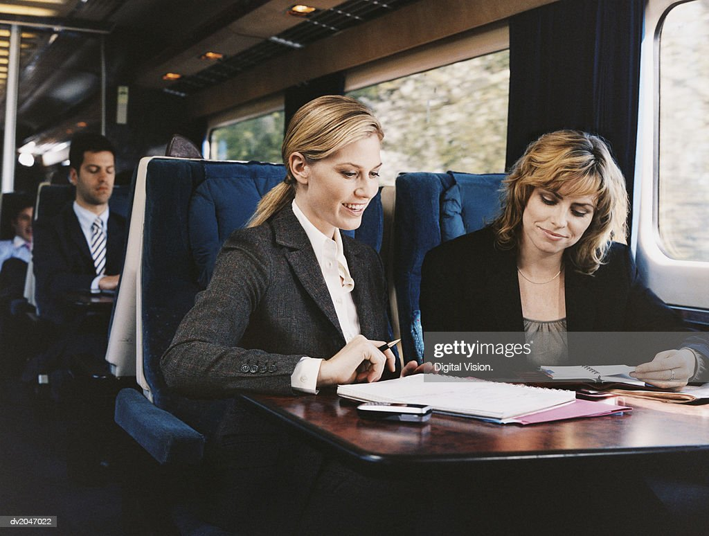 Two Female Business Executives Examining a Document on a Passenger Train : Stock Photo