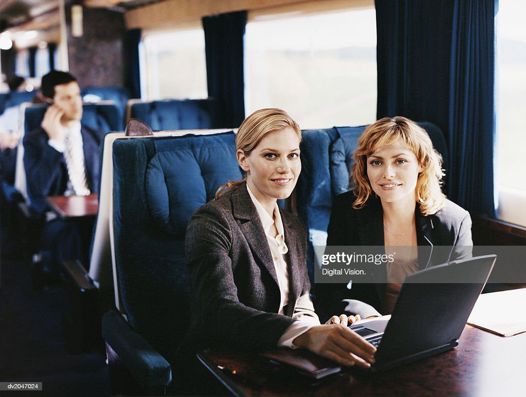 Two Female Business Executives With a Laptop on a Passenger Train : Stock Photo