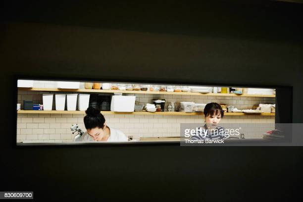 Two female chefs preparing for evening meal service in restaurant kitchen