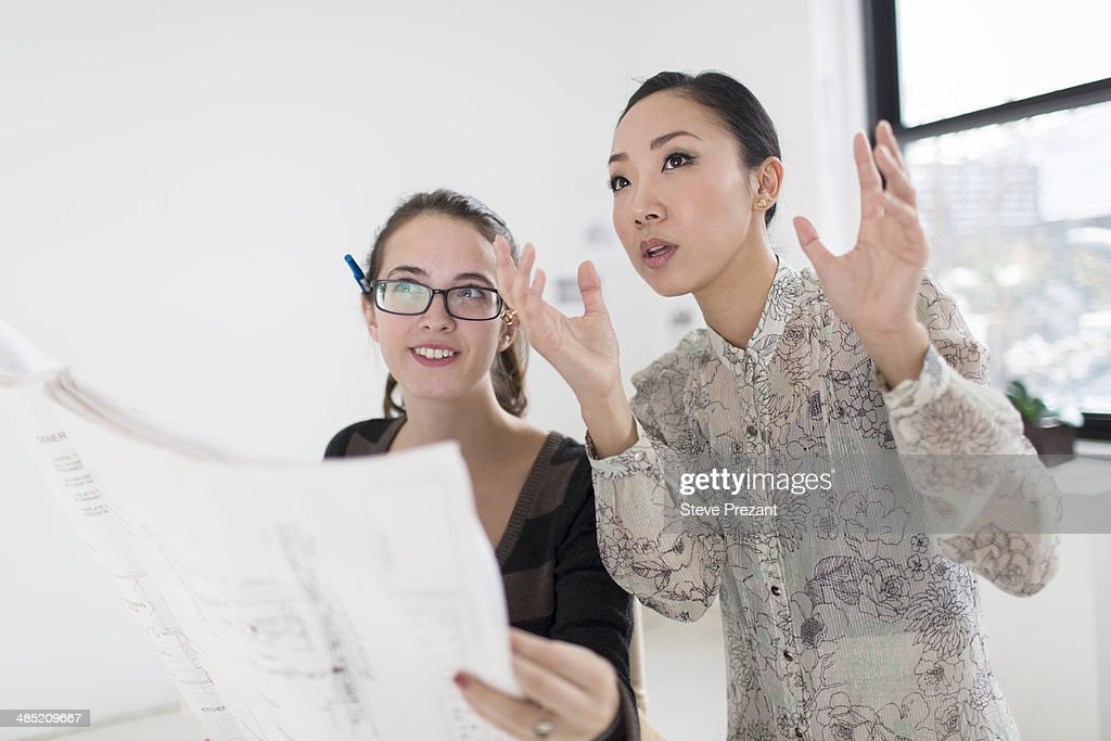 Two female colleagues discussing blueprint : Stock Photo