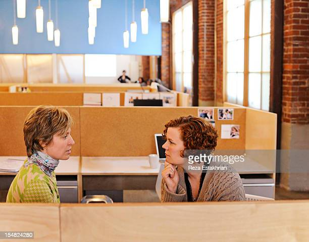 Two female colleagues in discussion at desk