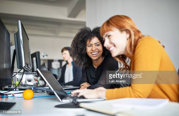 two female colleagues in office working together - arbeiten stock-fotos und bilder