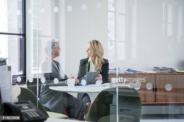 Two female colleagues sitting behind glass partition in modern office