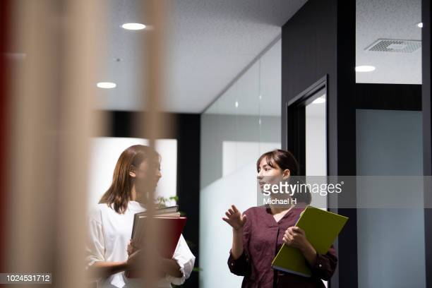 two female colleagues walking in office corridor - japanese ol ストックフォトと画像