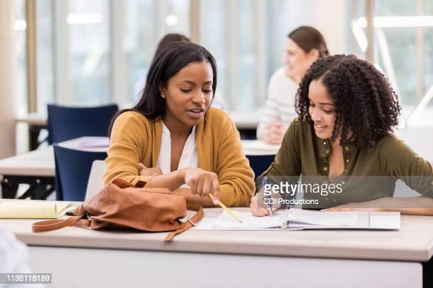 dois amigos universitários fêmeas estudam junto na biblioteca - figurantes incidentais - fotografias e filmes do acervo