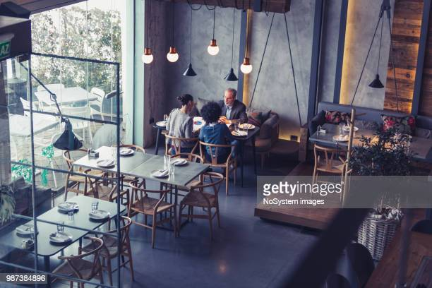 Two female collegues having business meeting in high end restaurant with senior client. Multi-ethnic group