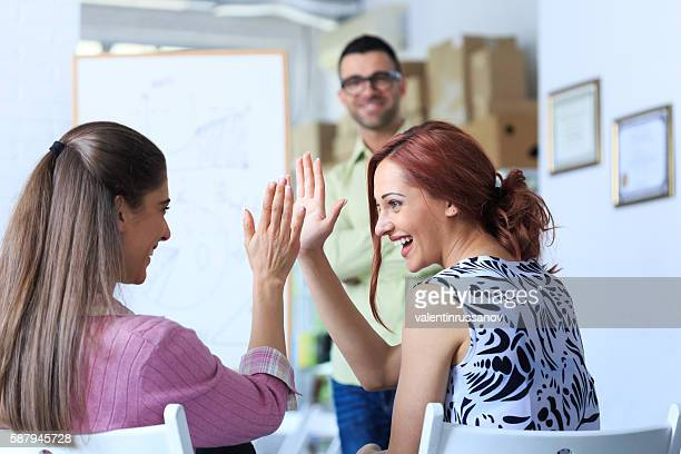 Two female coworkers giving high five at workplace
