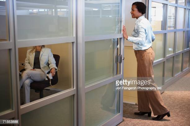 Two female coworkers talking in office