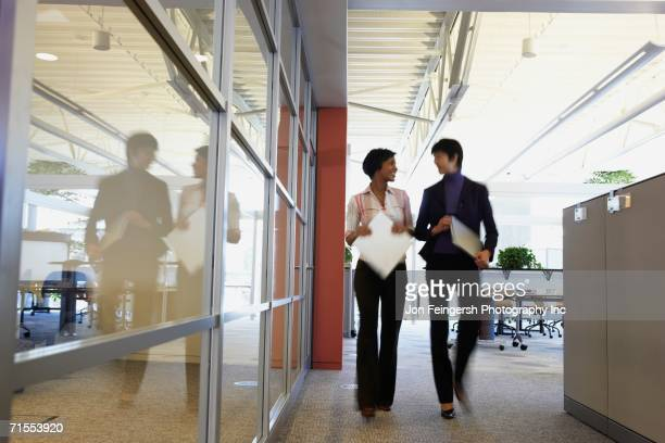 two female coworkers talking in office - striding stock pictures, royalty-free photos & images