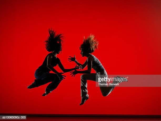two female dancers wearing street clothes leaping on stage - performing arts event stock pictures, royalty-free photos & images