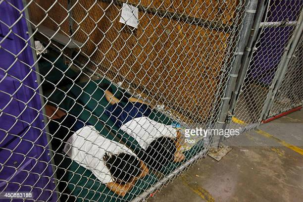 Two female detainees sleep in a holding cell as the children are separated by age group and gender as hundreds of mostly Central American immigrant...