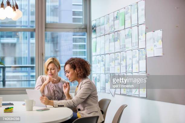 Two female digital designers looking at digital tablet at desk