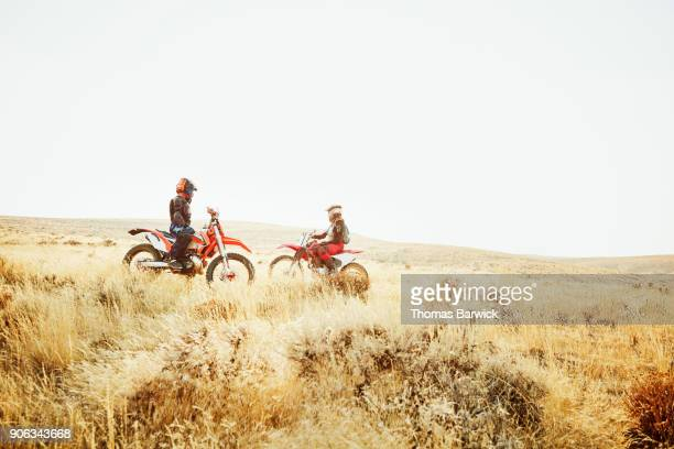 Two female dirt bike riders looking across rolling desert hills during summer evening ride