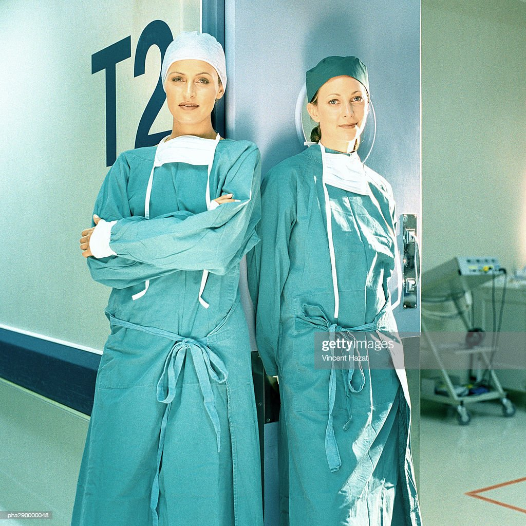 Two female doctors in operating gowns, leaning against doorframe : Stockfoto