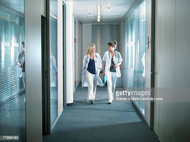Two female doctors walking in a lobby of a hospital.