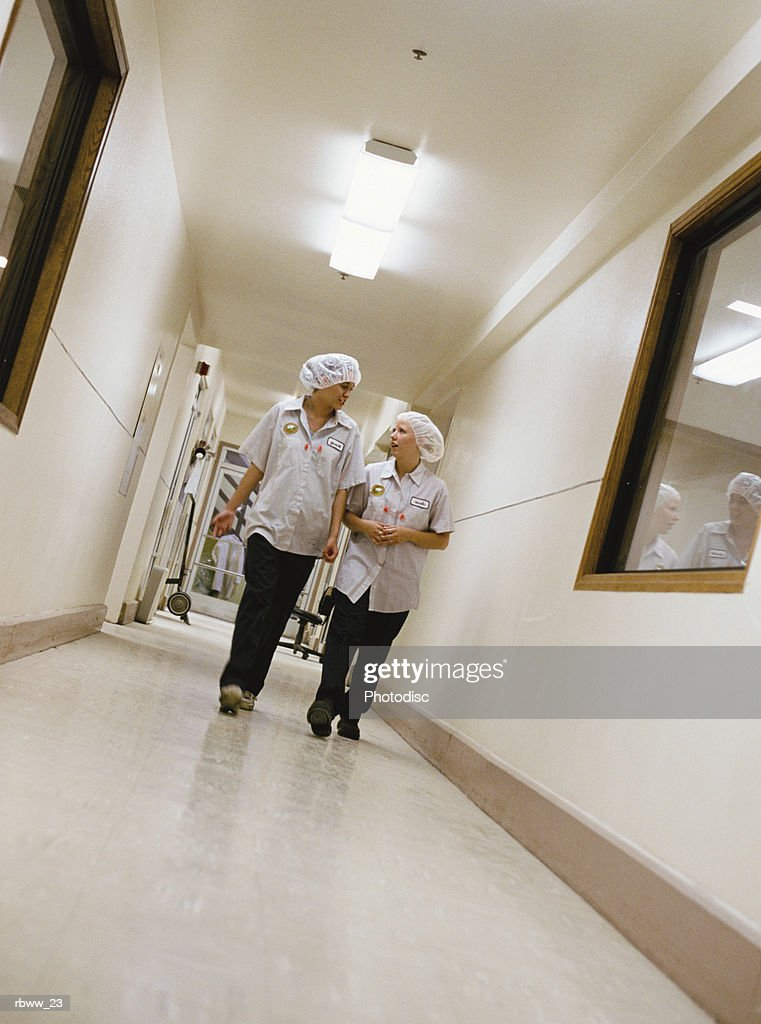 two female factory workers walk down a hallway : Foto de stock