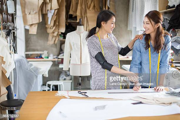 two female fashion designers talking in studio - side by side stock photos and pictures