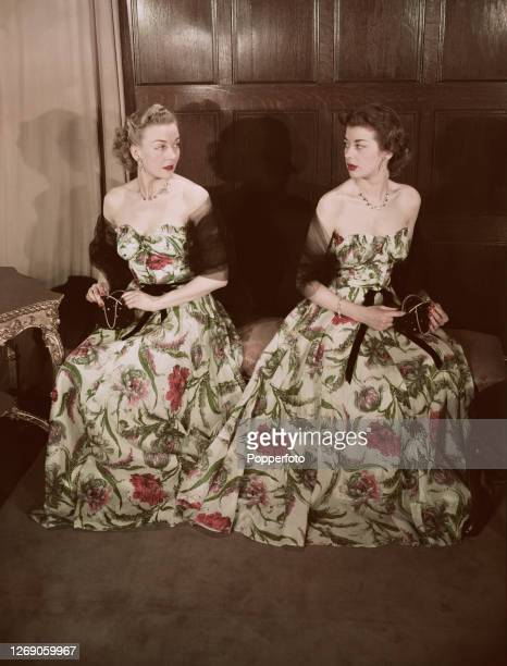 Two female fashion models wear identical off the shoulder dancing dresses with a tight bodice and a low waist in a floral fabric London May 1951