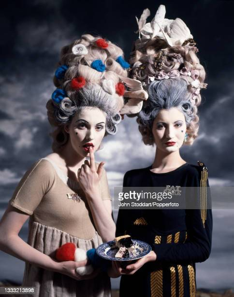 Two female fashion models wear outfits by John Galliano, comprising empire line wool dresses and brooches spelling 'Love To' and 'Eat Cake', both...