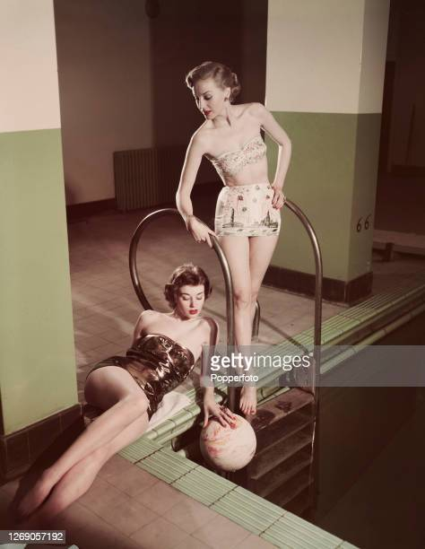 Two female fashion models wearing bathing suits and swimwear, one a metallic fabric, the other incorporating a Festival of Britain motif, both...