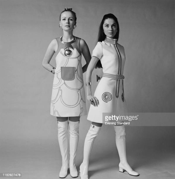 Two female fashion models wearing sleeveless short dress with printed design and necklace and short sleeves high neck dress with geometric designs...