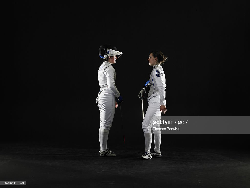 Two female (15-18) fencers facing off, side view : Foto de stock